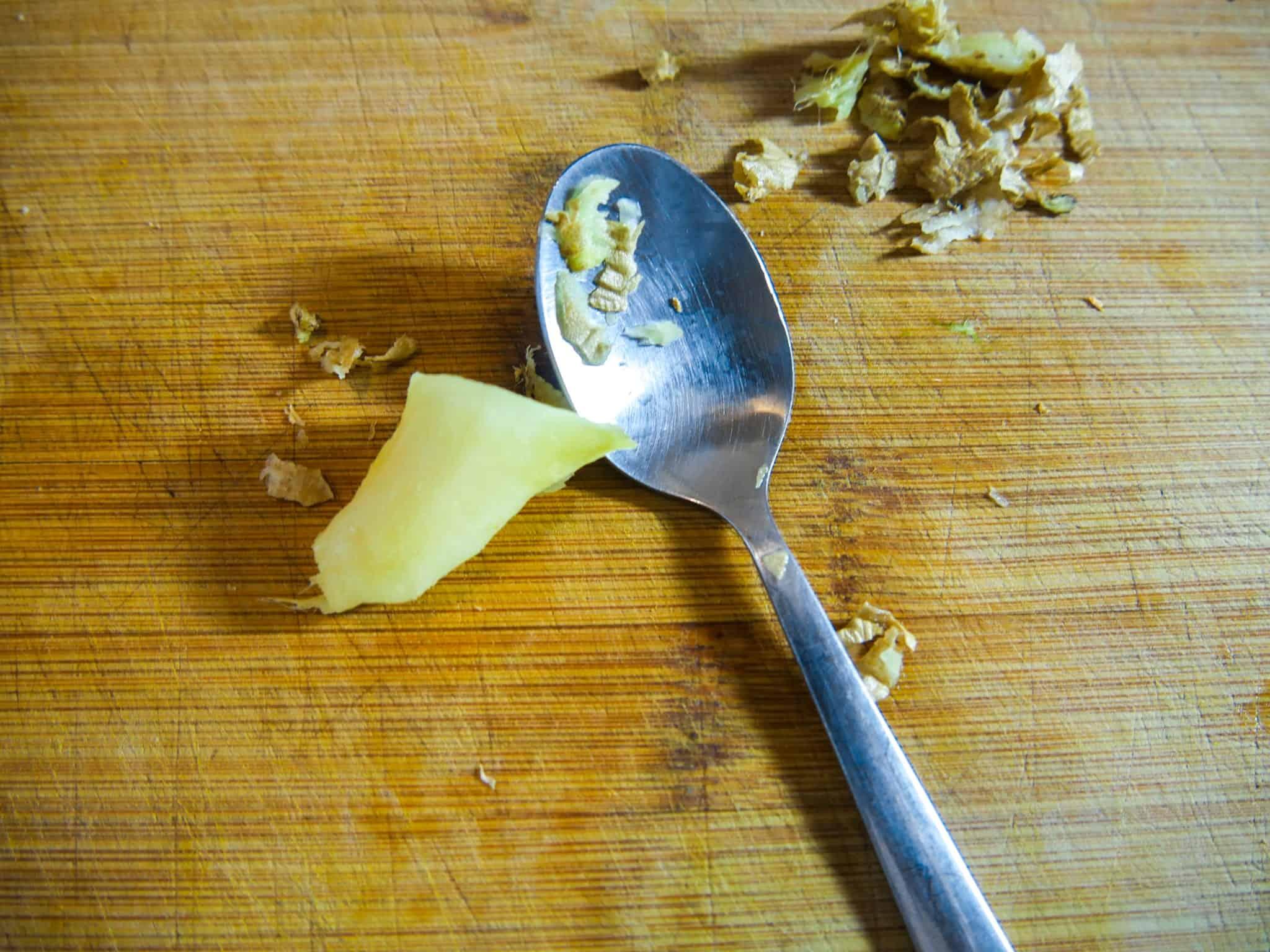 Ingwer für die leichte Kürbissuppe mit einem Löffel schälen